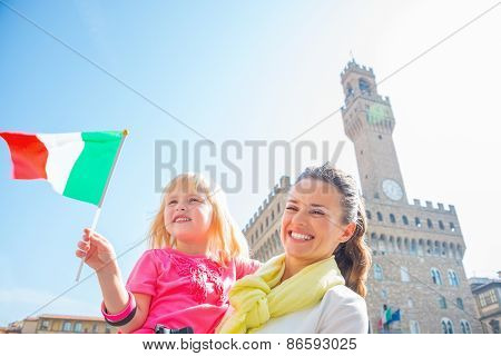 Happy Mother And Baby Girl With Flag In Front Of Palazzo Vecchio In Florence, Italy