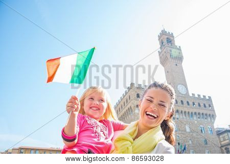Portrait Of Happy Mother And Baby Girl With Flag In Front Of Palazzo Vecchio In Florence, Italy