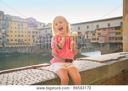 Happy Baby Girl Eating Ice Cream Near Ponte Vecchio In Florence,