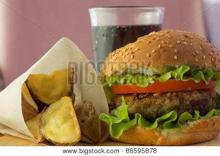 Burger, Potato Wedges And Cola On Wooden Plate