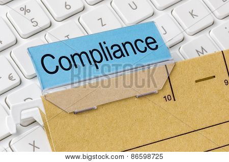 A Brown File Folder Labeled With Compliance