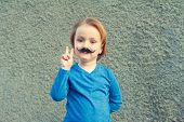 foto of peace-sign  - Young cute caucasian boy of 4 years old with a fake Italian moustache making a peace sign with his right hand standing in front of an old grey stone wall - JPG