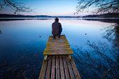 stock photo of pier a lake  - Small pier on lake with man silhouette - JPG
