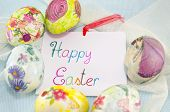 stock photo of decoupage  - Bunch of handcolored decoupage Easter eggs around a handwritten greeting card saying  - JPG