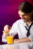 stock photo of bartender  - Young stylish man bartender preparing serving alcohol cocktail drink over bar counter - JPG