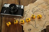 stock photo of survival  - Retro camera on world map with word Travel on wooden table background - JPG