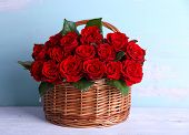 picture of wooden basket  - Bouquet of red roses in basket on wooden background - JPG