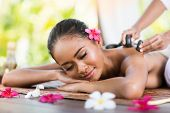 pic of therapist massage  - young woman receiving massage of back with stone massage - JPG