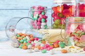 image of jar jelly  - Multicolor candies in glass jars on color wooden background - JPG