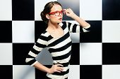 stock photo of chessboard  - Fashion shot of an elegant model in glasses posing in dress in black and white stripes on a background of black and white squares - JPG