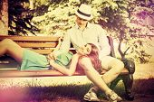 Picture of romantic young people tenderly talking on a park bench. Love concept.
