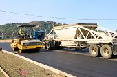 stock photo of paved road  - Drum tandem vibratory rollers compacting down a fresh layer of paving on a new road interchange project - JPG