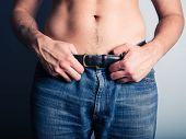 image of crotch  - A young man is grabbing the belt of his jeans - JPG