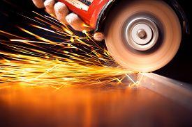 foto of sparking  - Worker cutting metal with grinder - JPG