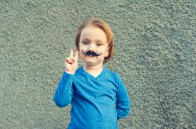 pic of moustache  - Young cute caucasian boy of 4 years old with a fake Italian moustache making a peace sign with his right hand standing in front of an old grey stone wall - JPG