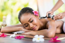 stock photo of thai massage  - young woman receiving massage of back with stone massage - JPG