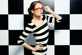 picture of shot glasses  - Fashion shot of an elegant model in glasses posing in dress in black and white stripes on a background of black and white squares - JPG