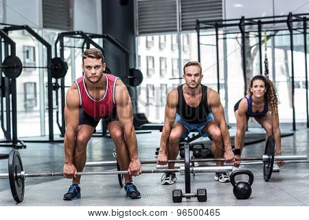Portrait of a three muscular athletes lifting a barbell