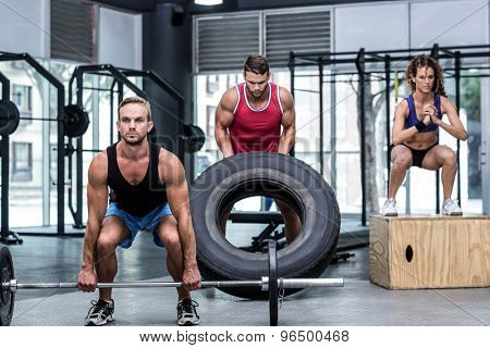 Serious three muscular people lifting and jumping in crossfit gym