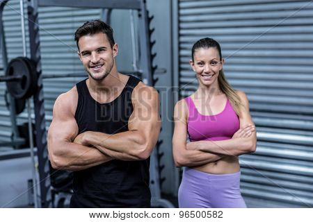 Portrait of a smiling muscular couple with arms crossed