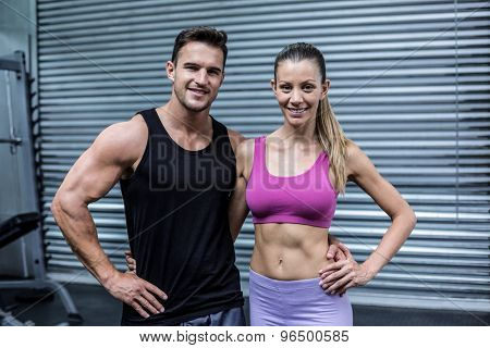 Portrait of a smiling muscular couple with arms around