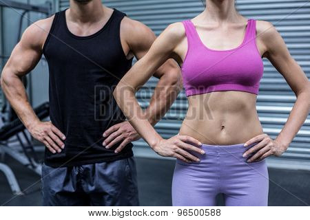 Muscular couple with hands on the hips at the crossfit gym