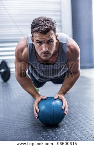 Portrait of a Muscular man on a plank position with a ball