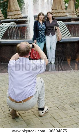 Man Taking A Photo Of Women At A Fountain