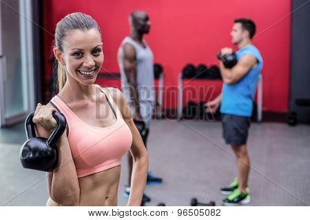 Portrait of a smiling muscular woman lifting a kettlebell