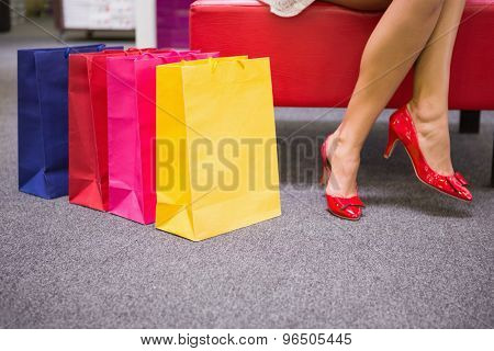 Woman sitting with legs crossed next to shopping bags at a shoe store