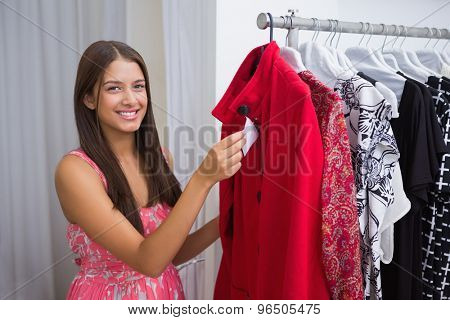 Portrait of smiling woman holding price tag and looking at camera at a boutique