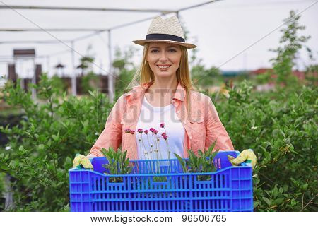 Pretty farmer in hat holding floral seedlings