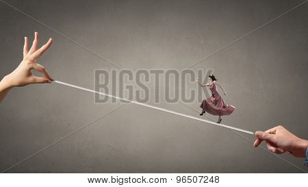 Woman in evening dress and blindfold walking on rope