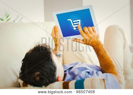 Man laying on sofa using a tablet pc against trolley