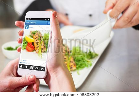 Hand holding smartphone against chef pouring sauce on salmon dish