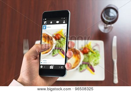 hand holding smartphone against high angle view of lasagna with potatoes and salad