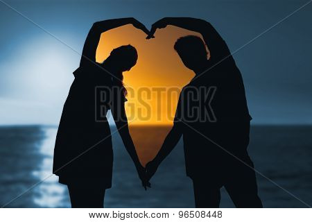 sunset of a beautiful day against happy couple forming heart shape with their hands