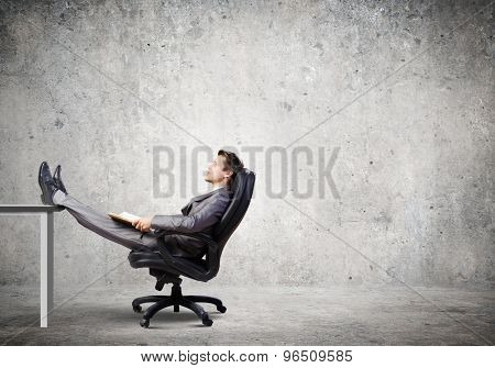 Confident handsome businessman sitting in chair and dreaming
