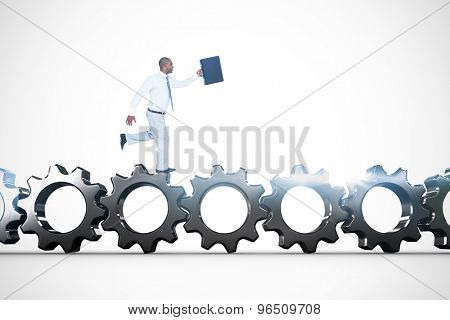Businessman running with briefcase against metal cogs and wheels connecting