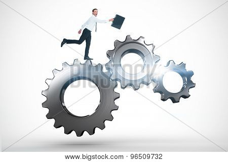 Happy businessman leaping with his briefcase against metal cogs and wheels connecting