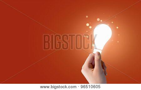 Close up of human hand holding light bulb