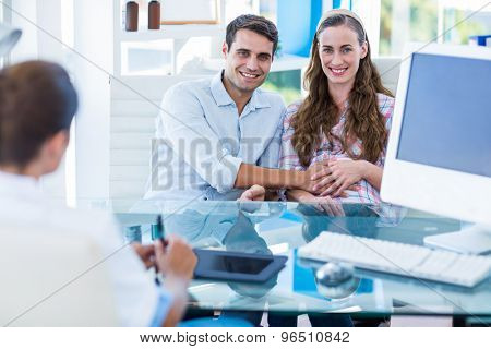 Pregnant woman and her husband smiling at camera in an examination room