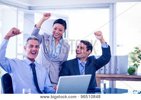 Happy business people cheering together in office