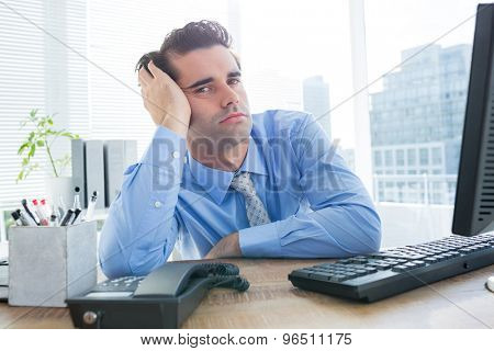 Serious young businessman looking at cameara in office