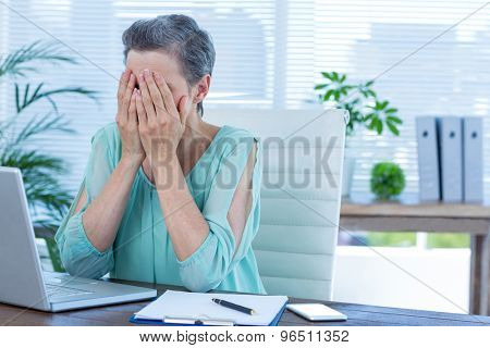 Anxious businesswoman with head in hands at office