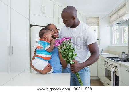 Happy smiling couple with his babyboy in the kitchen