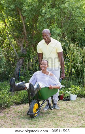 Happy smiling couple playing with wheelbarrow at home in garden