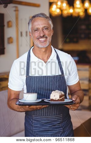 waiter smiling and holding tray at the coffee shop