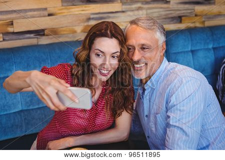 Couple taking a selfie in cafe