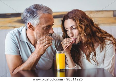 cute couplehaving glass of orange juice at the cafe